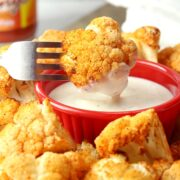 A fork dunking a piece of roasted cauliflower into ranch dressing.