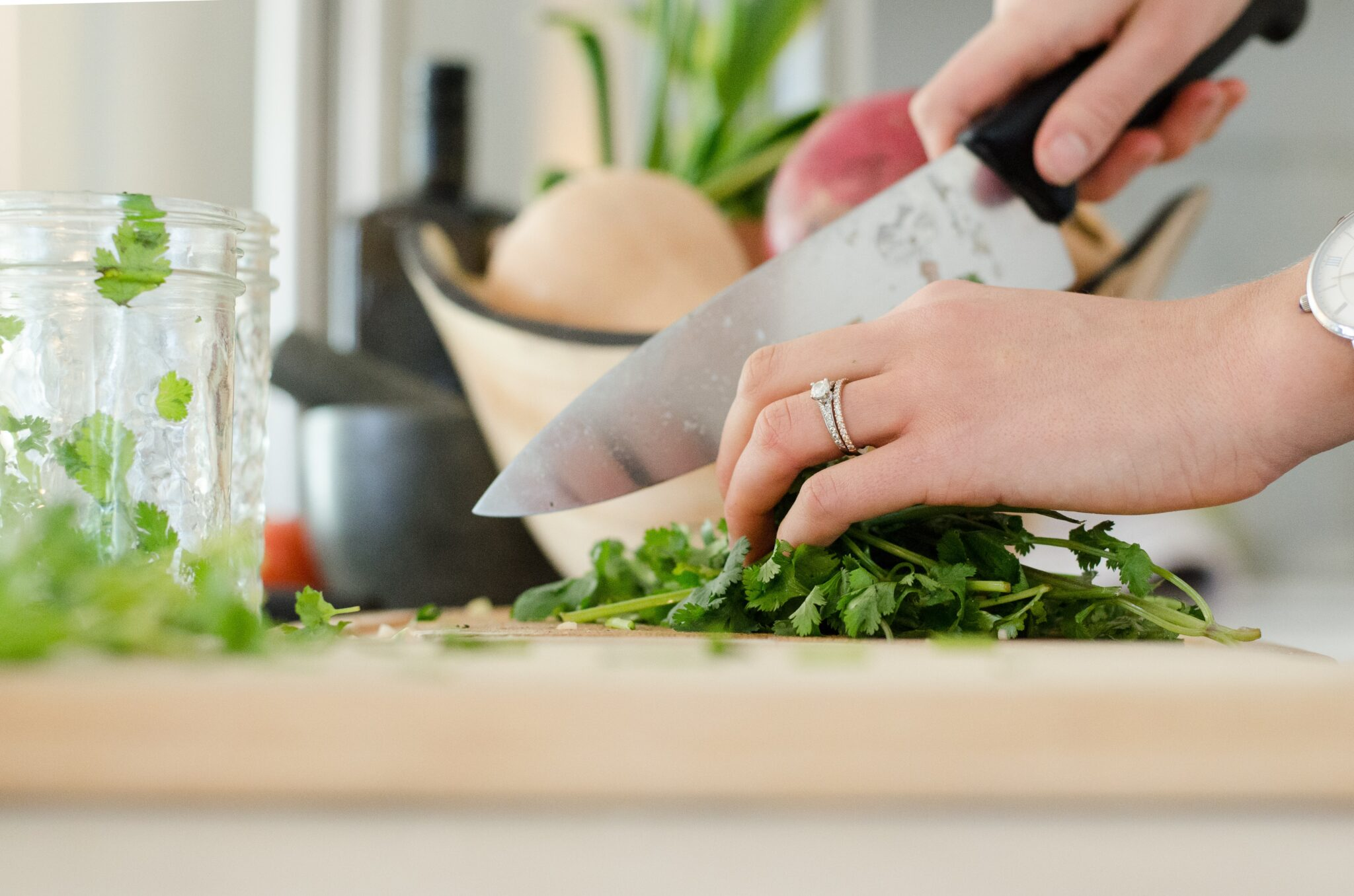 Hands holding a knife, chopping greens on a cutting board.