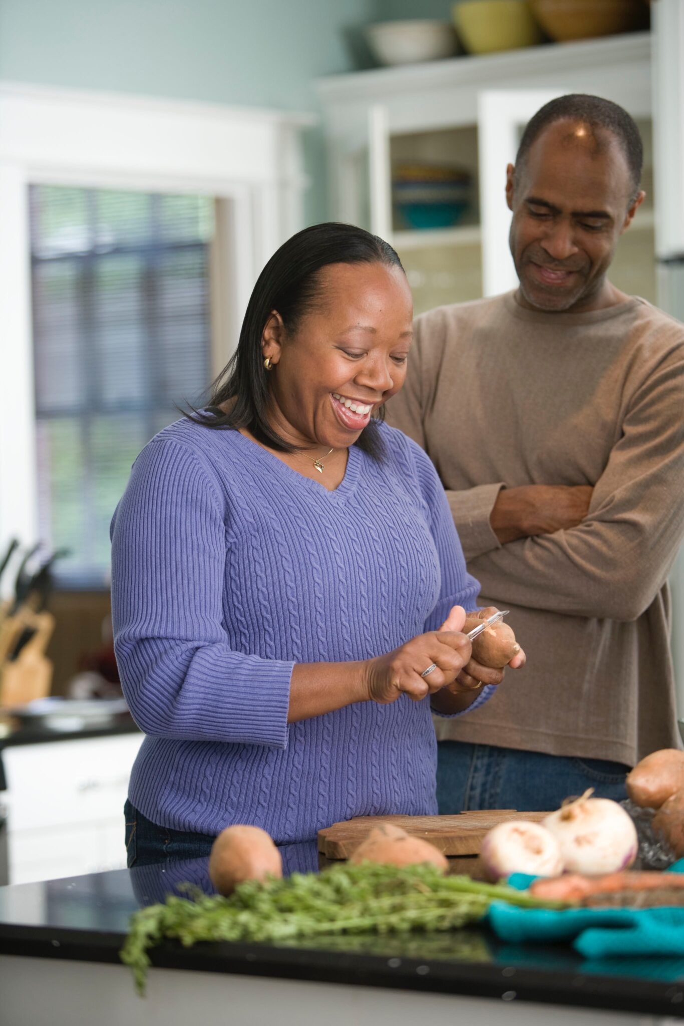 A woman peeling potatoes with man in kitchen.