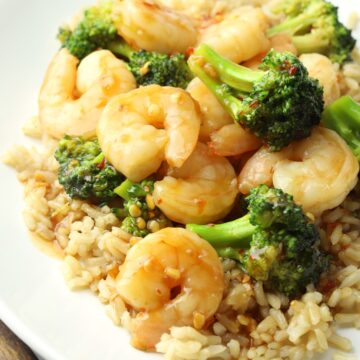A white plate with shrimp, broccoli, and rice.