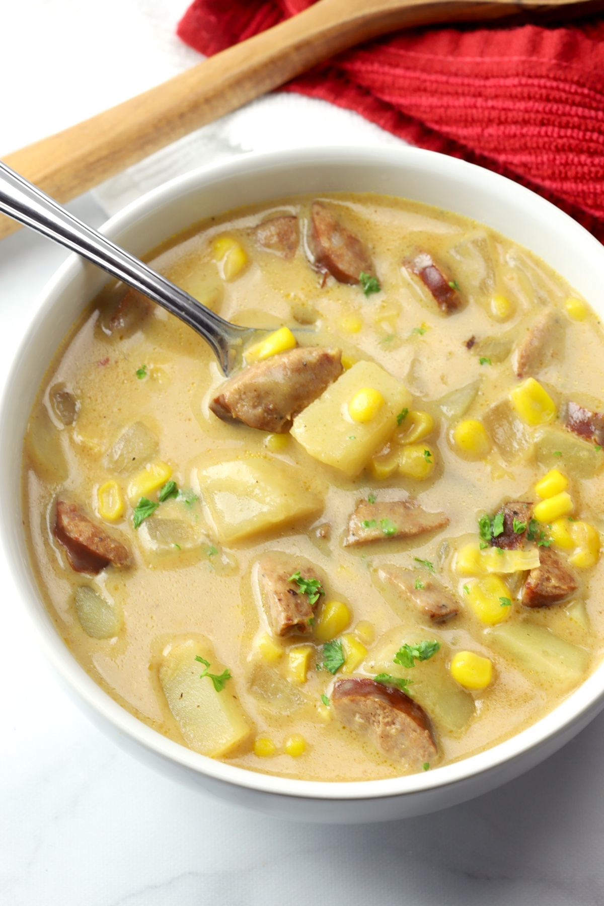 A white bowl filled with corn chowder with andouille sausage.