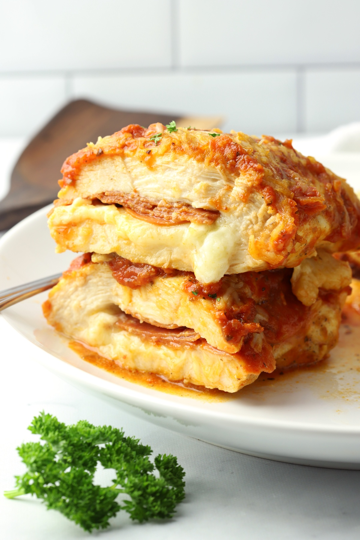 Chicken breast cut in half with pepperoni and cheese in the middle.