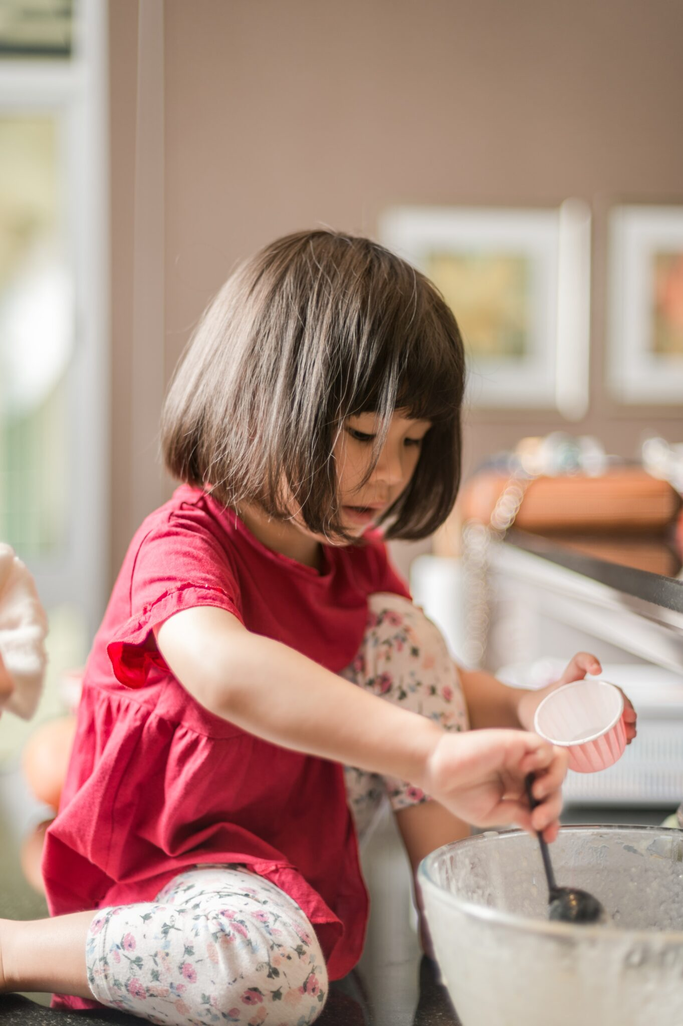 Girl in red t-shirt is helping bake cupcakes at home.