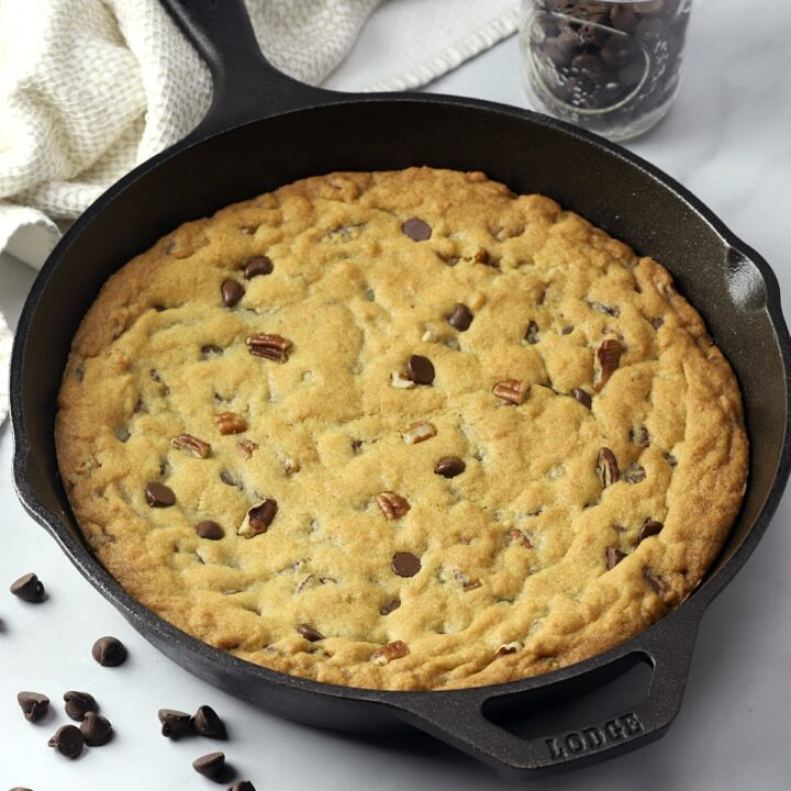A cast iron skillet with a cookie baked inside.