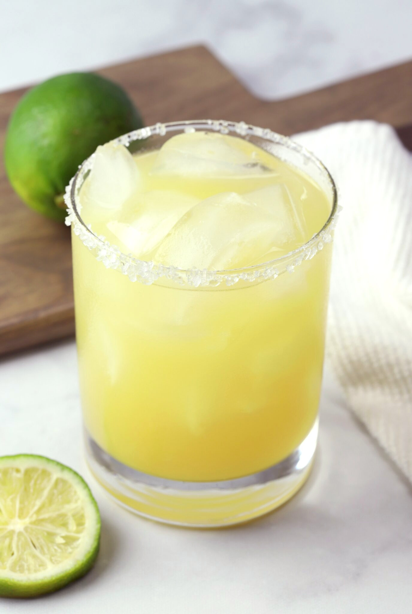 A pineapple margarita in lowball glass.