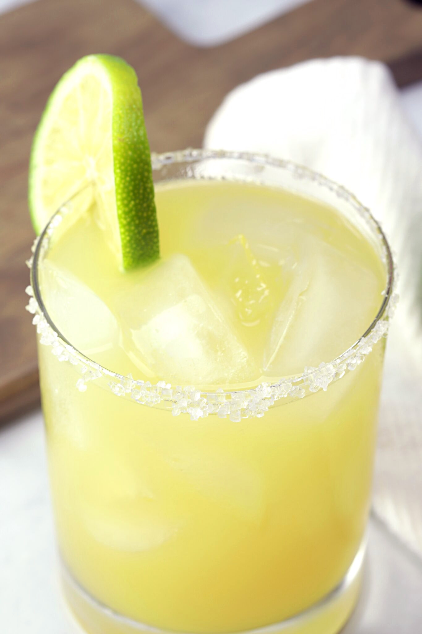 A yellow cocktail with salted rim and lime wedge.