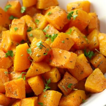 Butternut squash cubed and topped with fresh parsley.