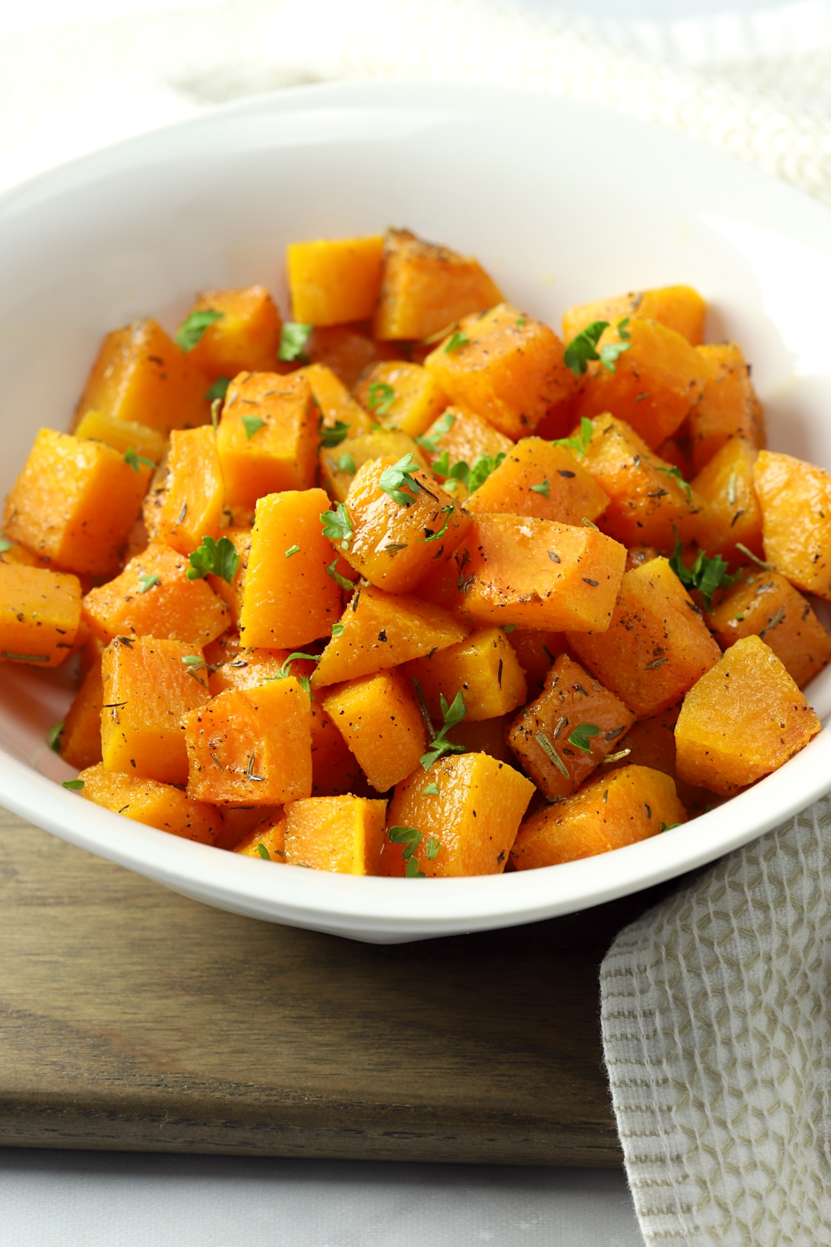 A white serving bowl filled with roasted butternut squash.