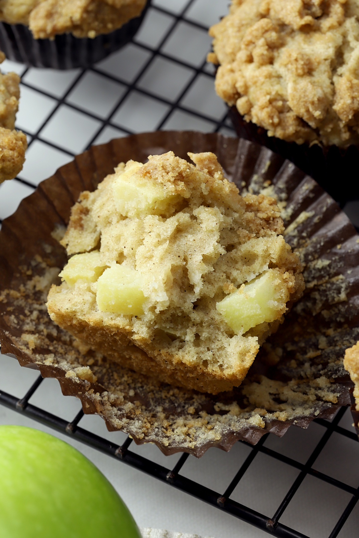 A muffin torn in half to show apple pieces.