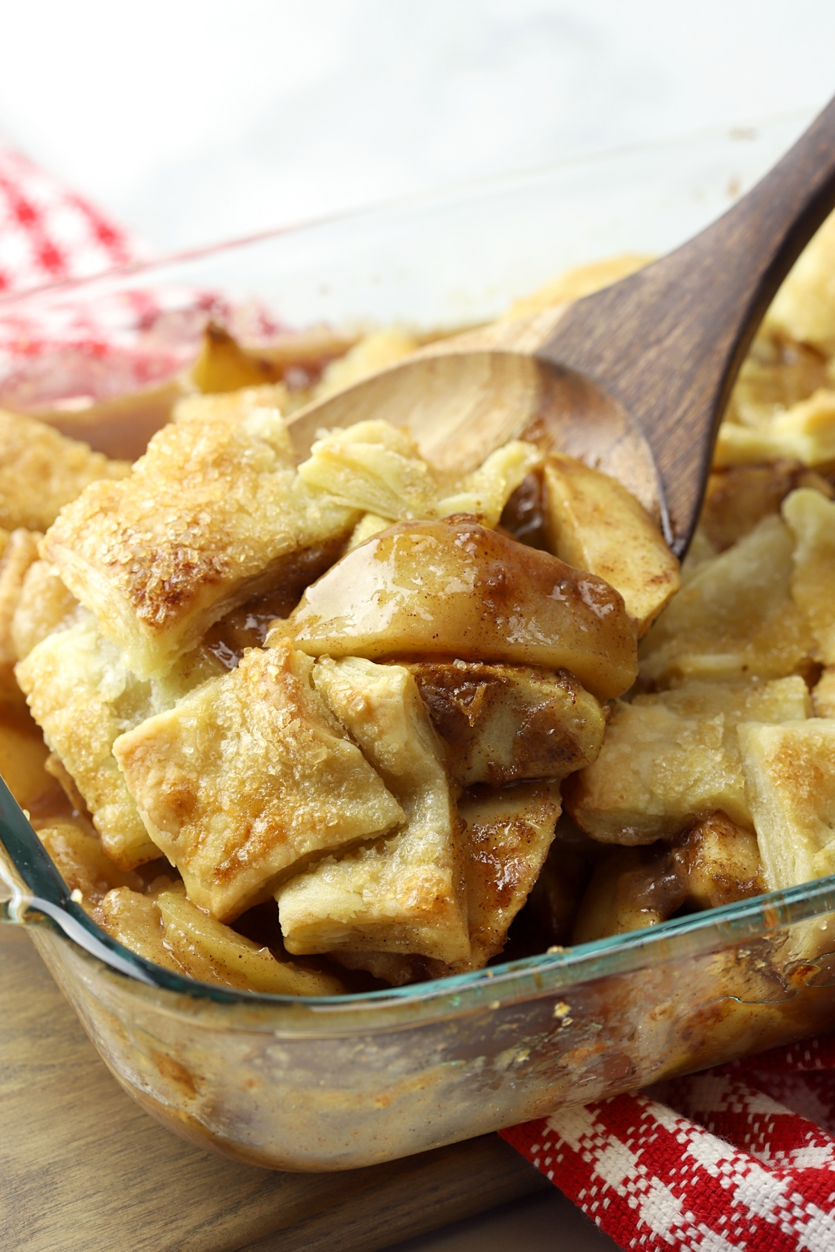 Wooden spoon scooping cooked apples and puff pastry out of a dish.
