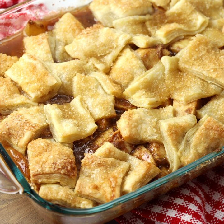 Puff pastry on top of apple pie filling in a glass dish.