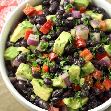 A white bowl filled with black beans, red peppers, and avocado.