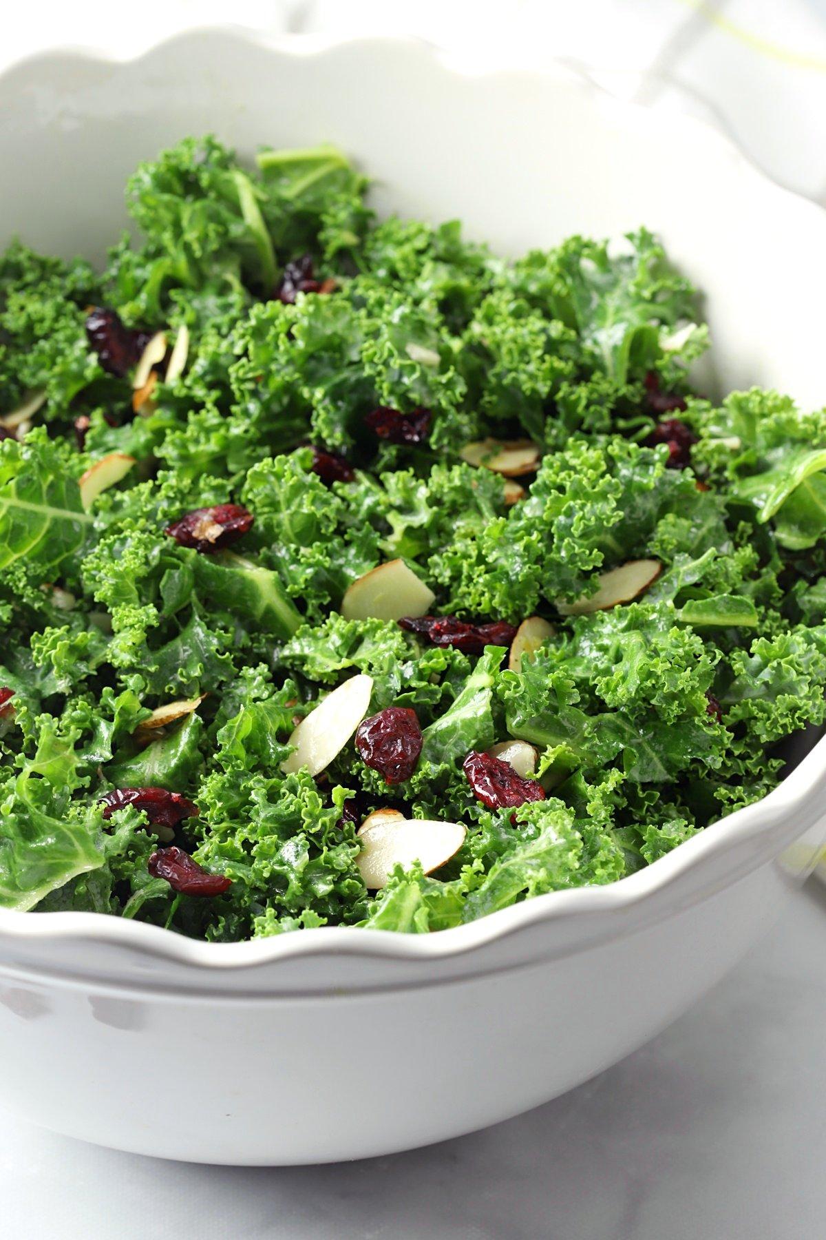Kale salad in a white, scalloped edge bowl.