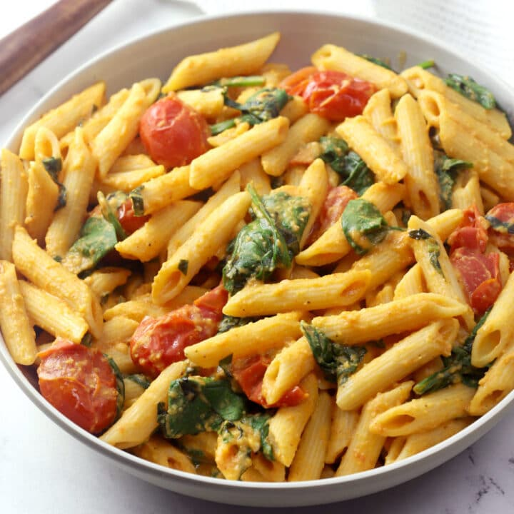 Bowl of penne pasta with spinach and cherry tomatoes.