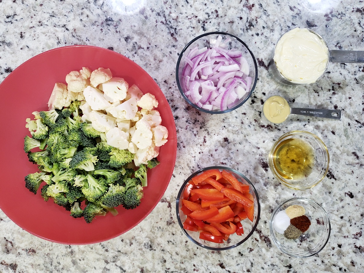 Vegetables and dressing ingredients in bowls on a counter top.