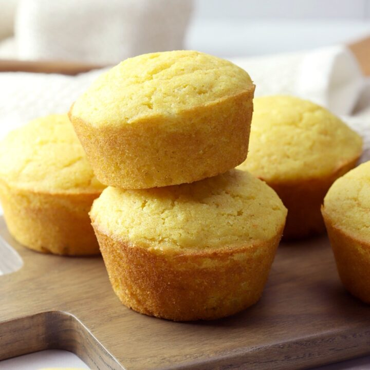 Two cornbread muffins stacked on a wooden cutting board.