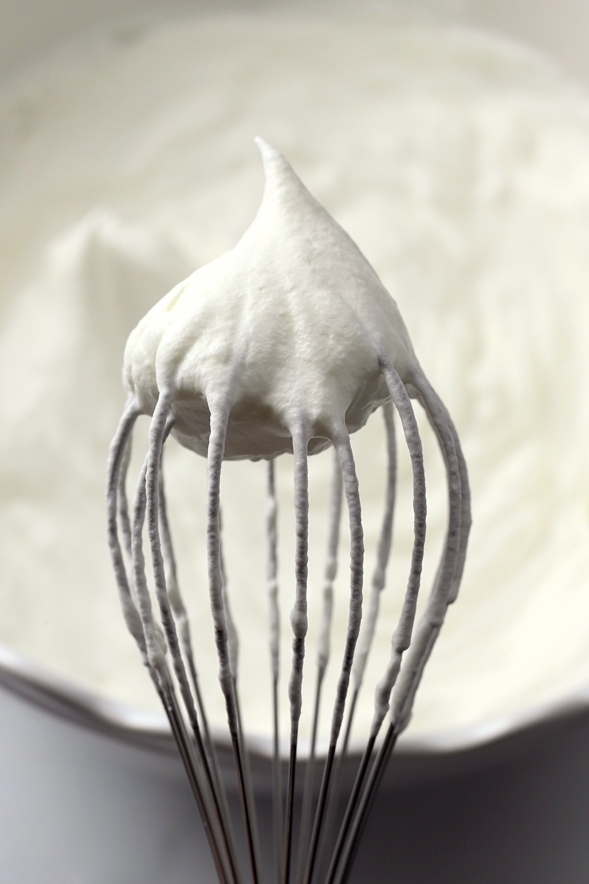 A whisk with a dollop of whipped cream on top.