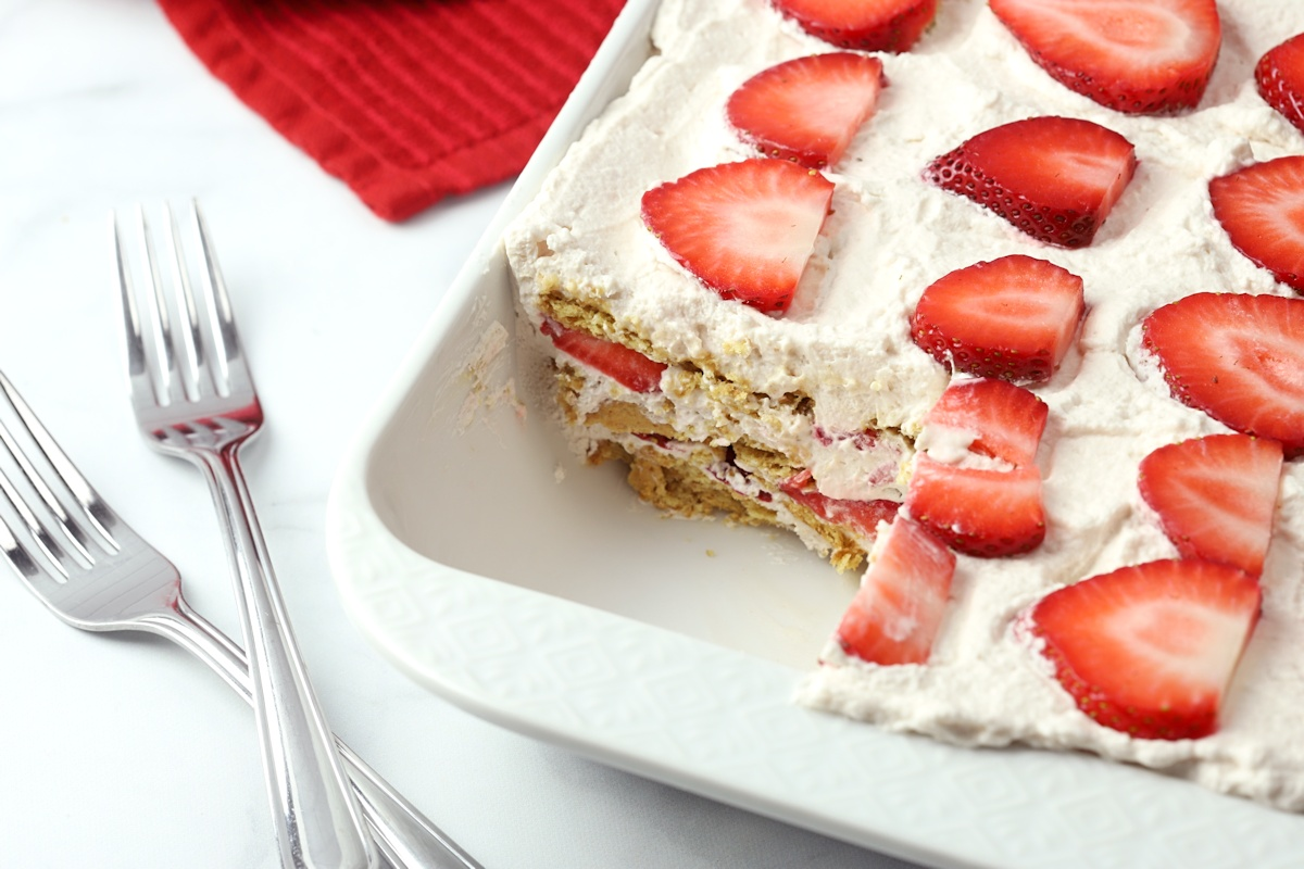 Strawberry icebox cake with one piece removed, alongside two forks.