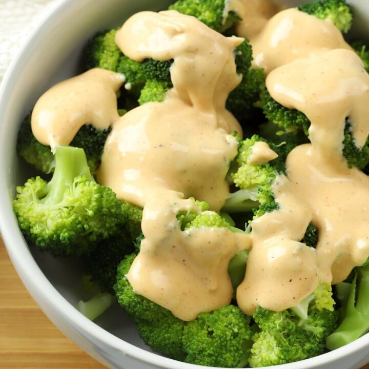 A white bowl filled with broccoli, topped with cheese sauce.