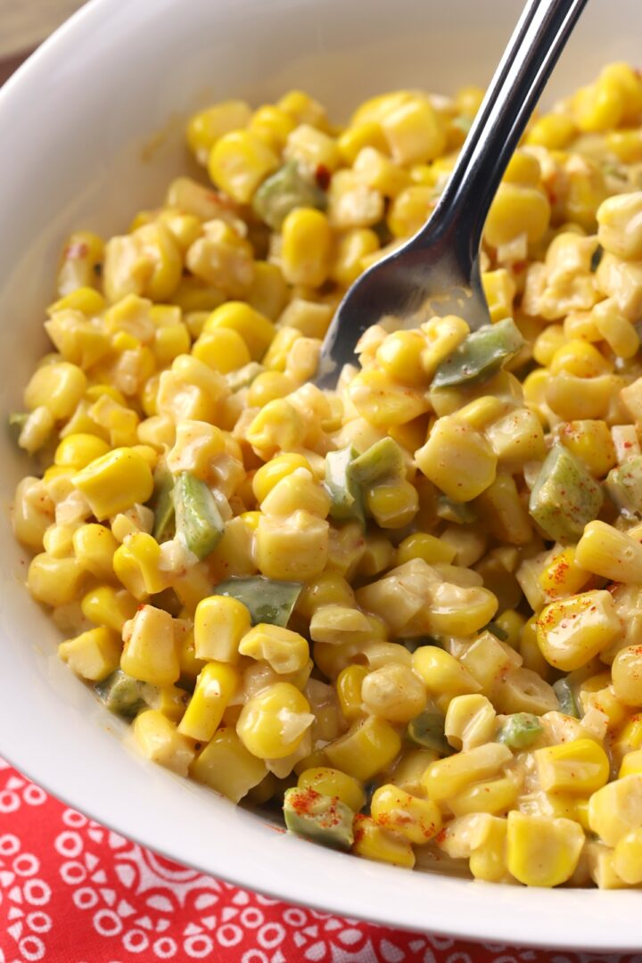 A fork stirring creamy corn in a bowl.