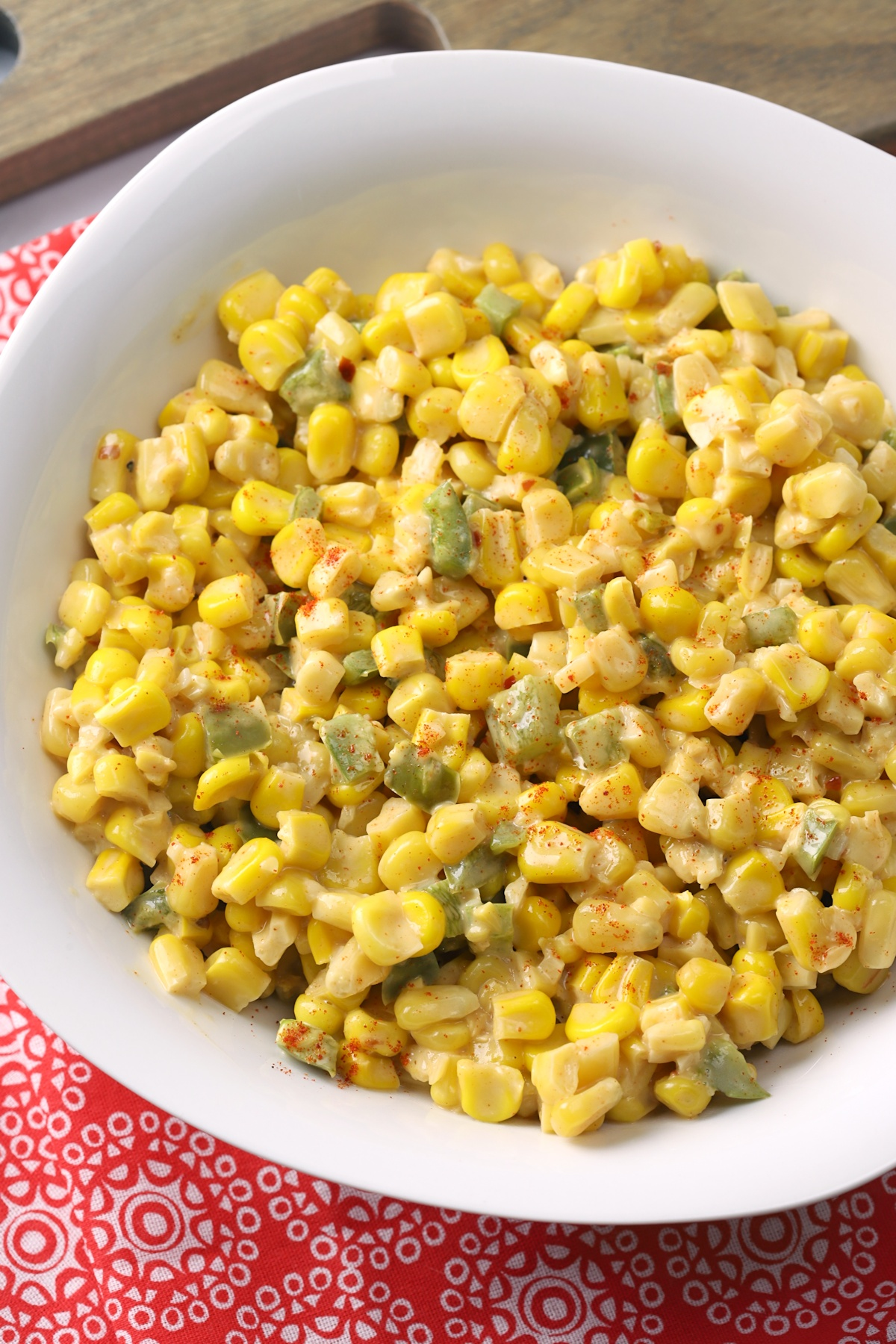 A white bowl filled with corn and jalapenos.