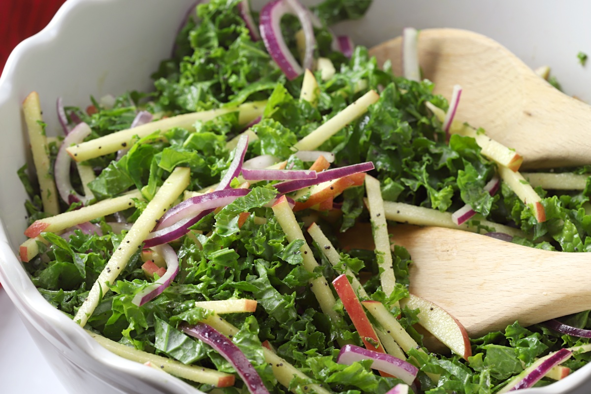 Kale slaw being tossed with wooden utensils.