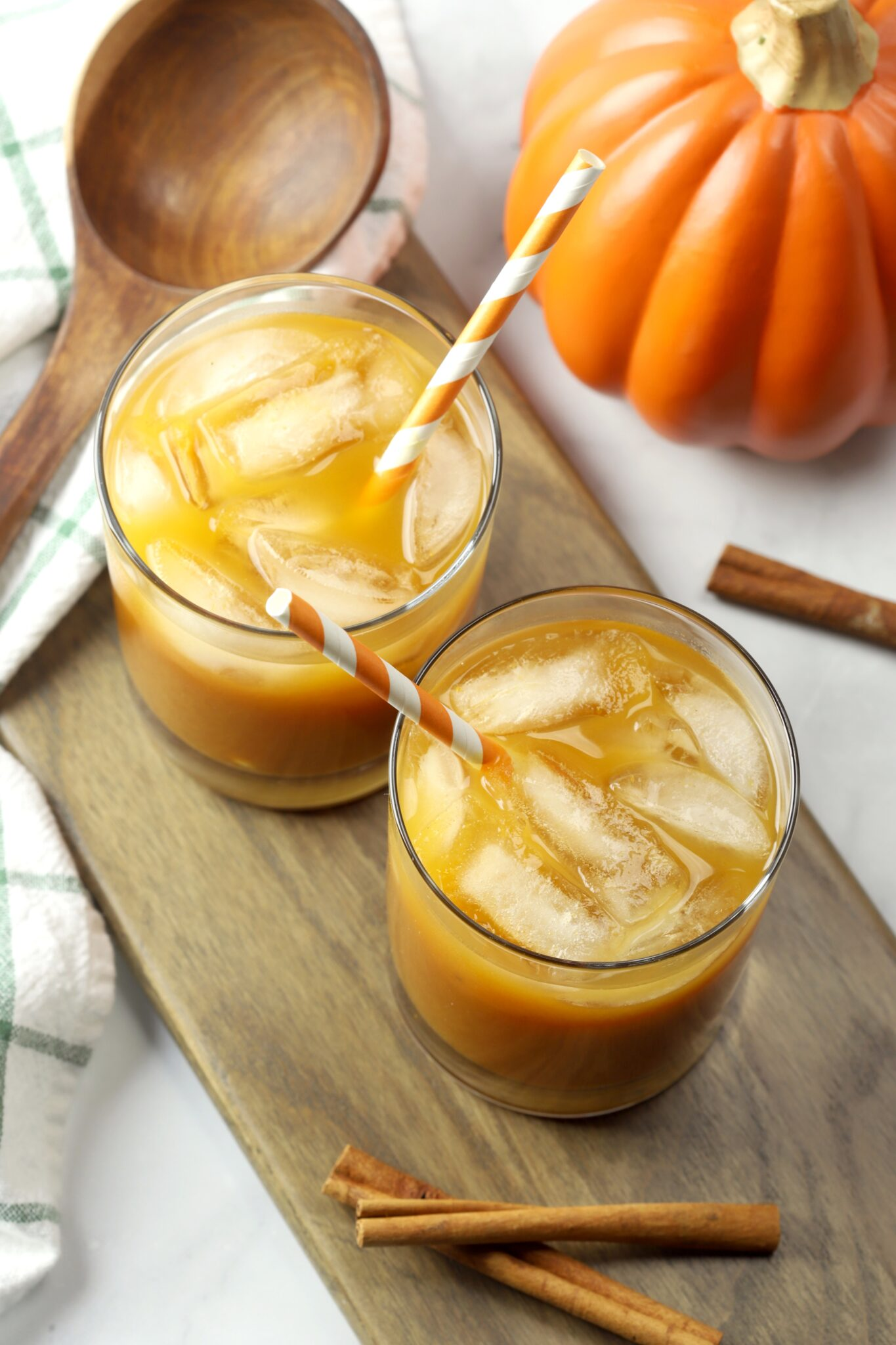 Two glasses of pumpkin juice on a wooden cutting board with orange striped straws.