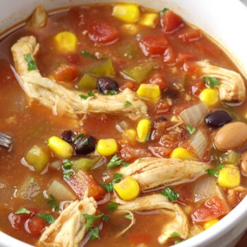 Chicken, beans, corn, and tomatoes in a broth.