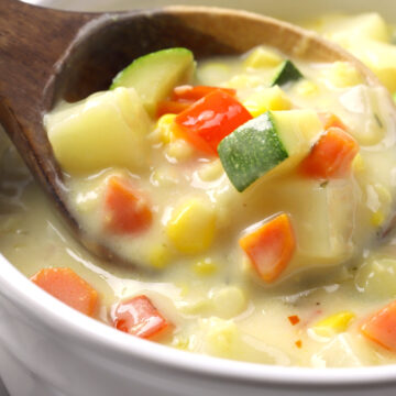 A wooden ladle filled with corn chowder.