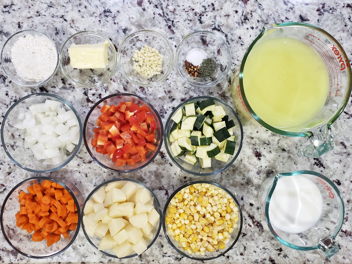 Ingredients, including summer vegetables like zucchini and corn, on a counter top.