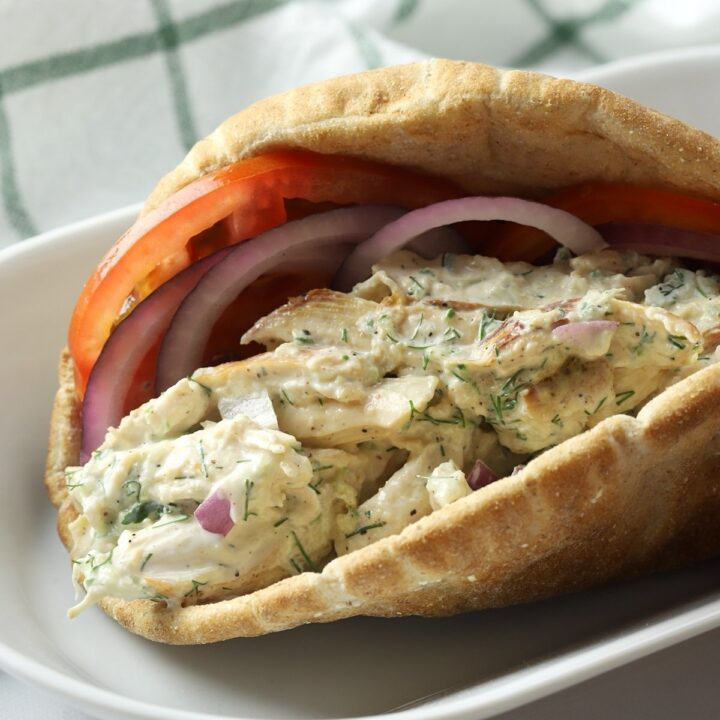 Pita bread filled with chicken salad, tomato slices, and red onion.