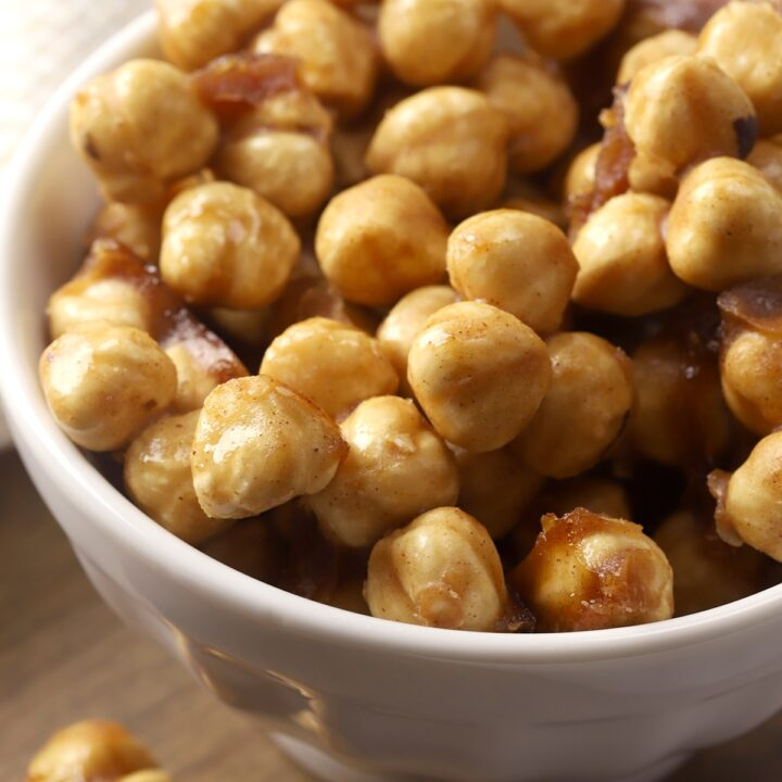 A white decorative bowl filled with candied hazelnuts.