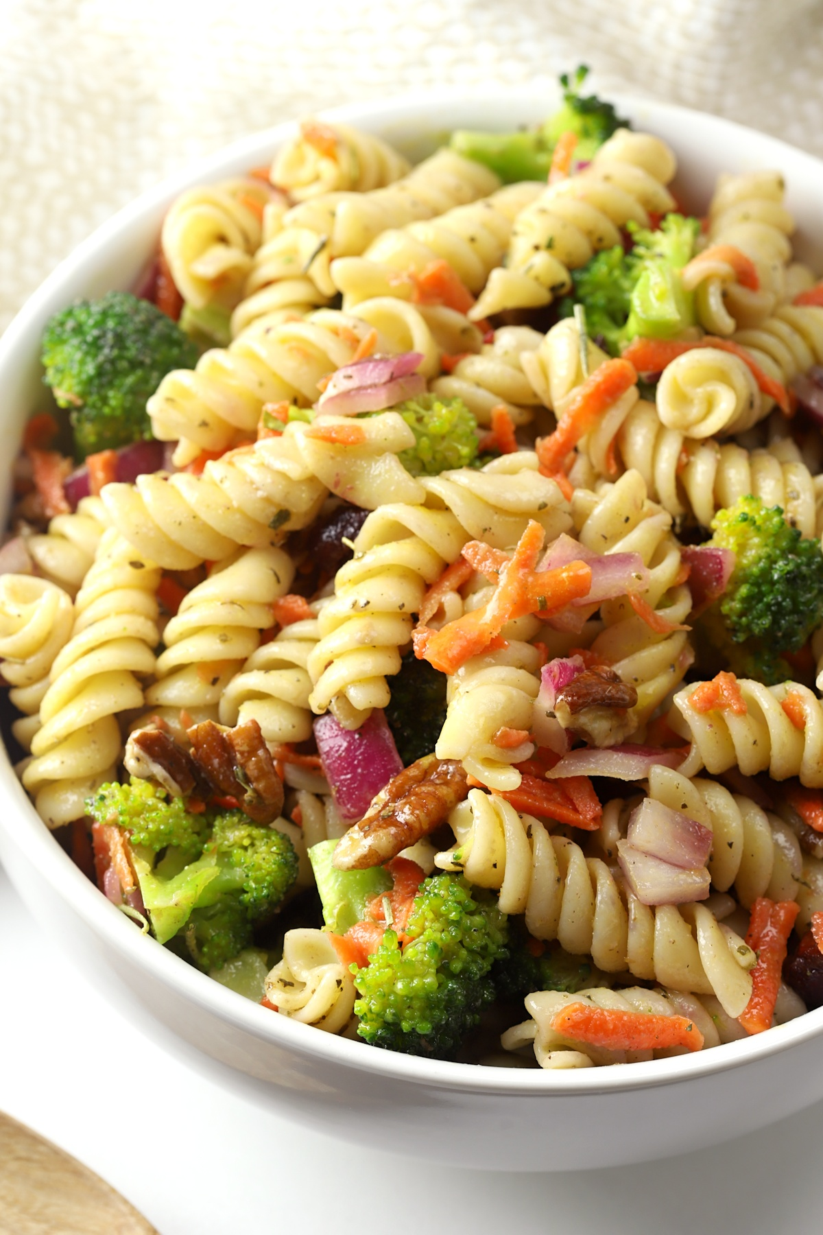 Rotini pasta tossed with grated carrots, broccoli, pecans, and cranberries.