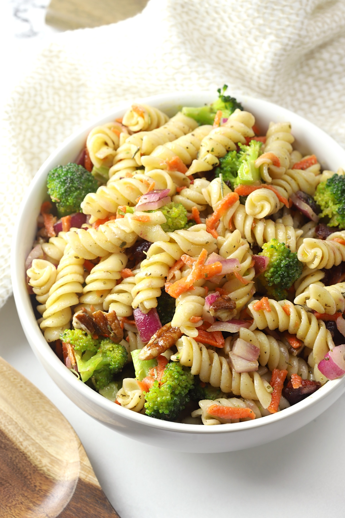 A white bowl filled with pasta salad.