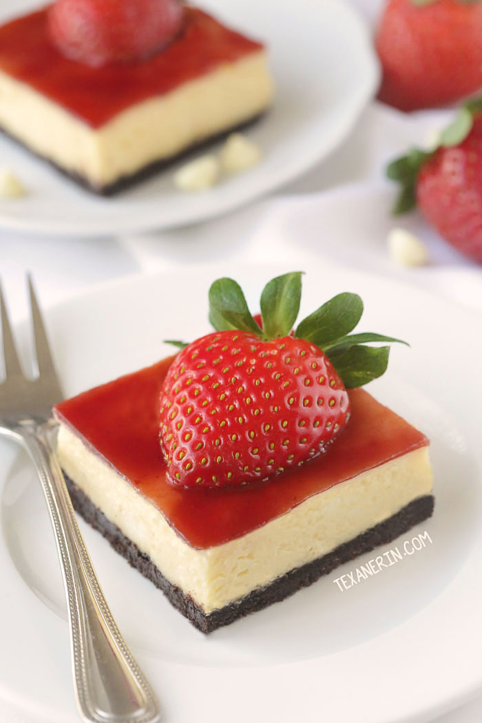 A strawberry cheesecake bar on a plate with a fork.