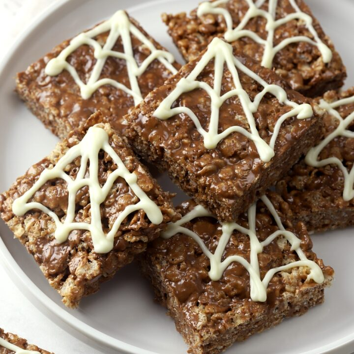 Chocolate rice krispies treats decorated with chocolate spider webs.