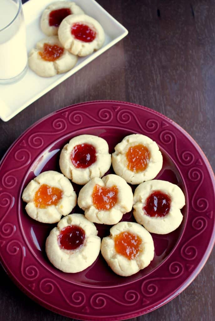 thumbprint cookies on a red plate.