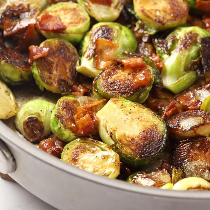 Brussels sprouts and bacon in a metal pan.