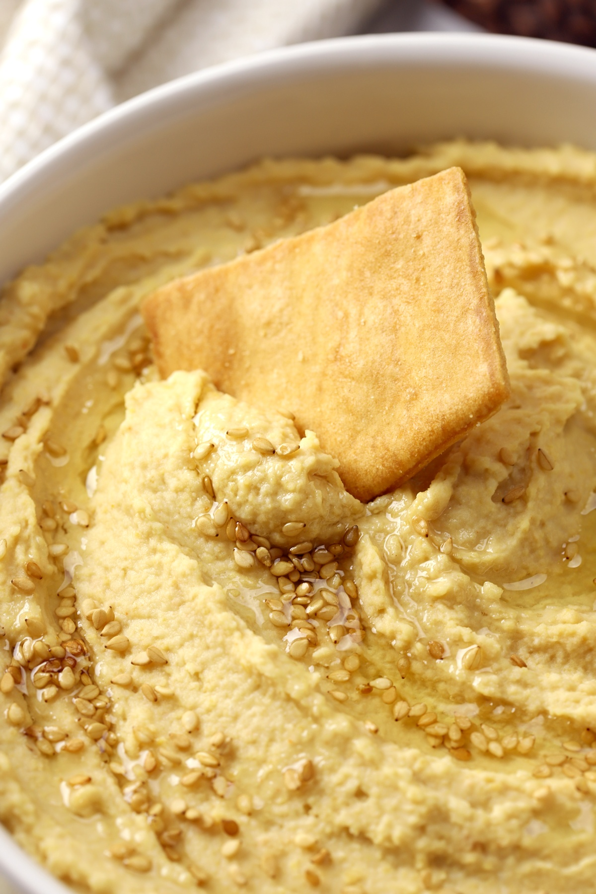 Pita chip scooping hummus out of a bowl.