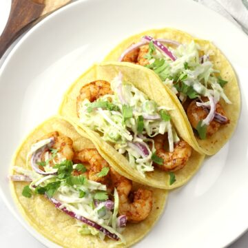 Three shrimp tacos on a white plate.
