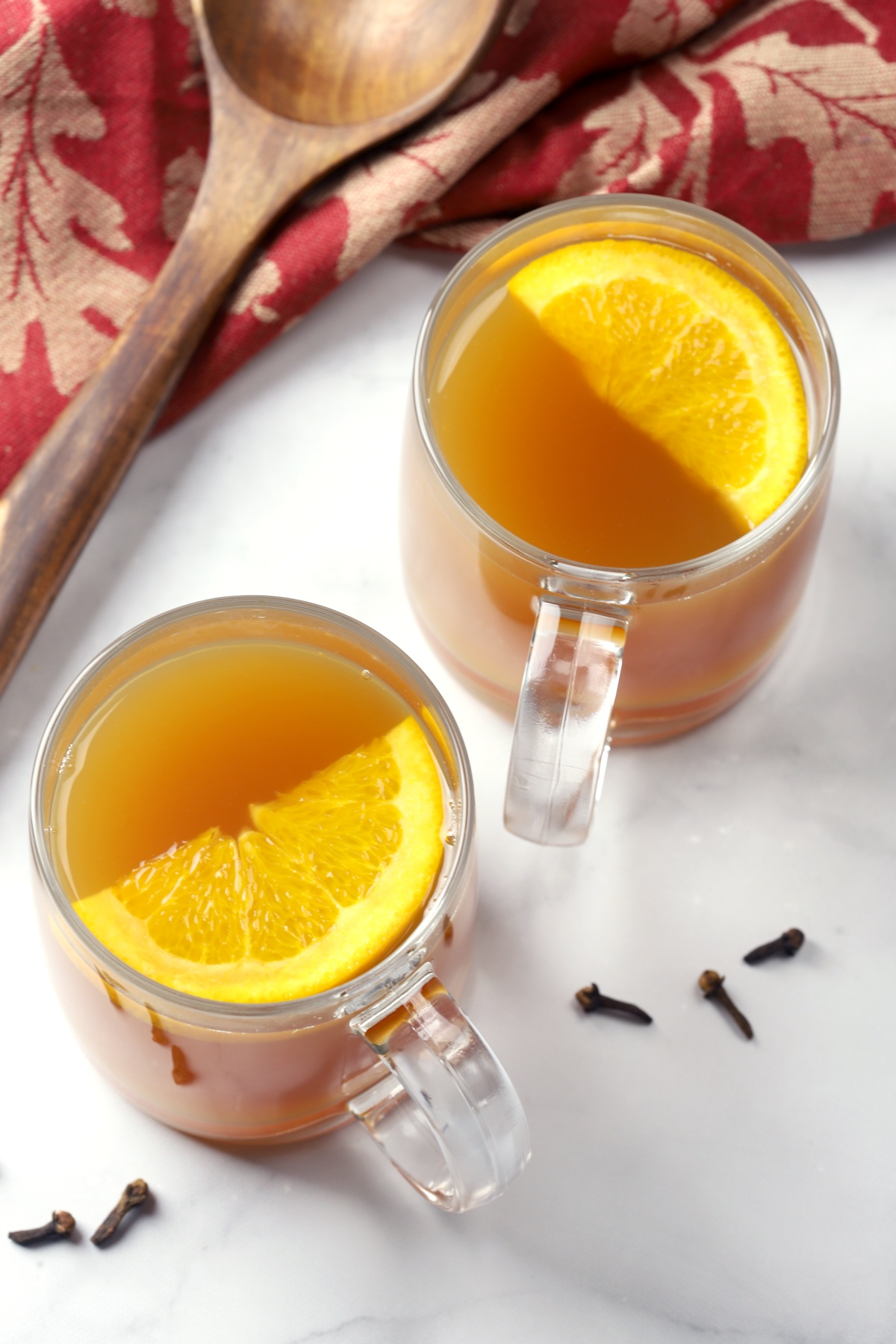 Two glass mugs filled with cider and topped with an orange slice.