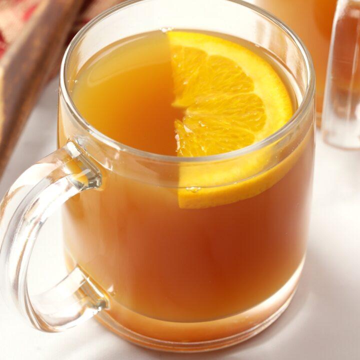 Glass mug filled with apple cider, garnished with an orange slice.