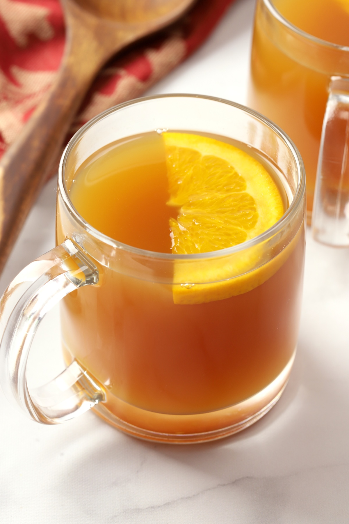 Glass mug filled with apple cider, garnished with an orange slice.