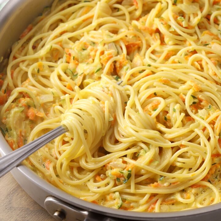 Saute pan with a fork swirling spaghetti.