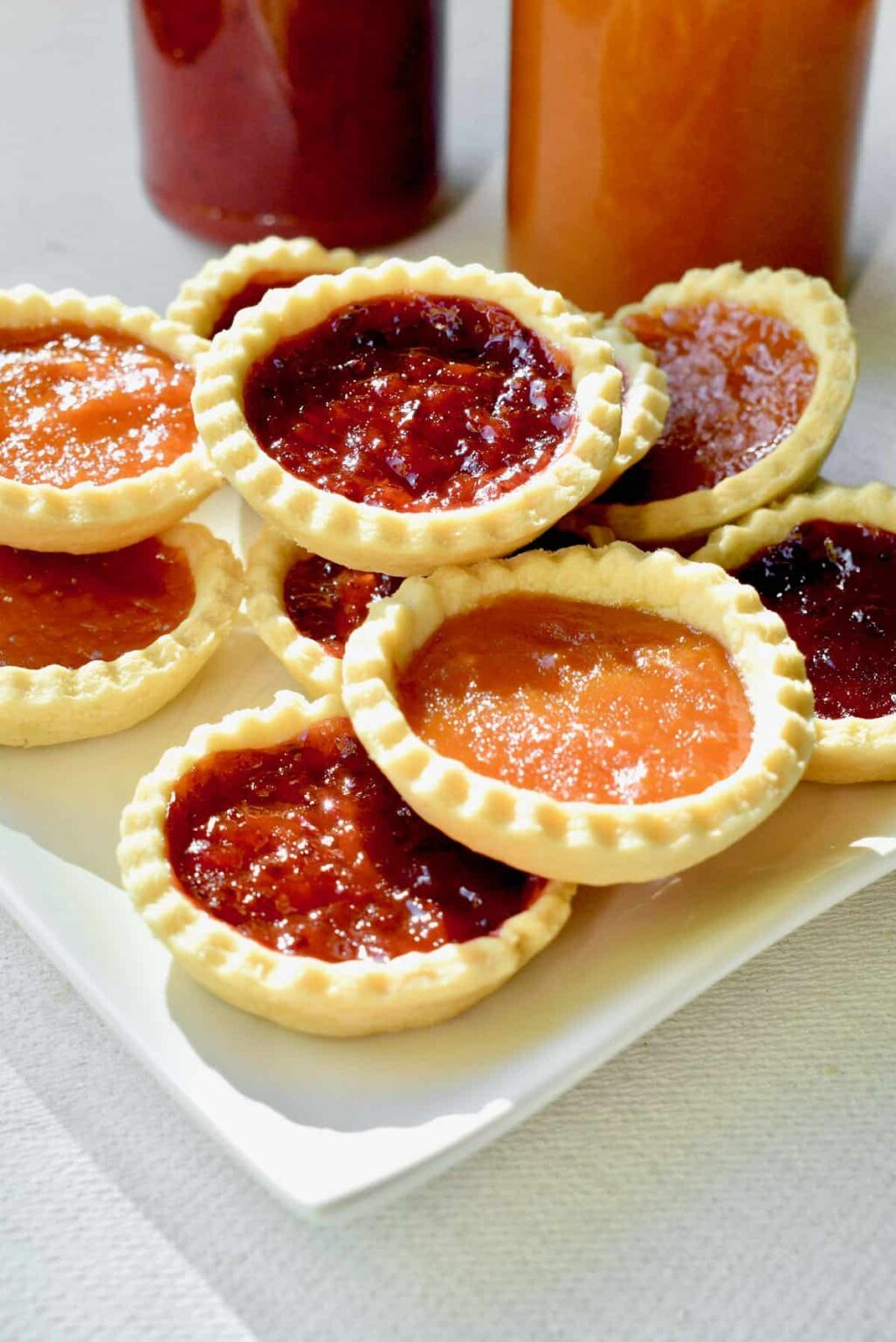 Jam tarts stacked on a white plate.