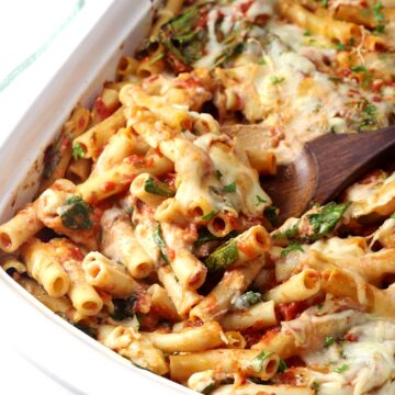 Wooden spoon scooping ziti from a casserole dish.