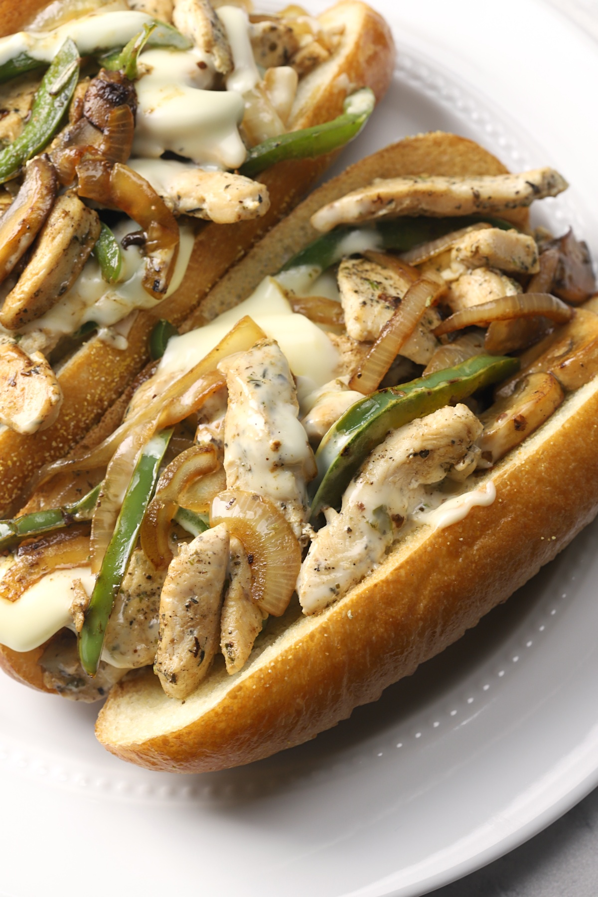Close up of onion, bell pepper, mushroom, and melty cheese on a chicken cheesesteak.