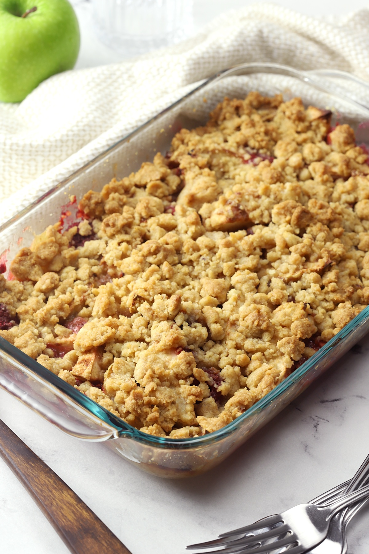 Glass casserole dish filled with baked apple raspberry crumble.