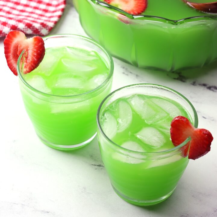 Bowl of punch with two glasses of grinch punch.
