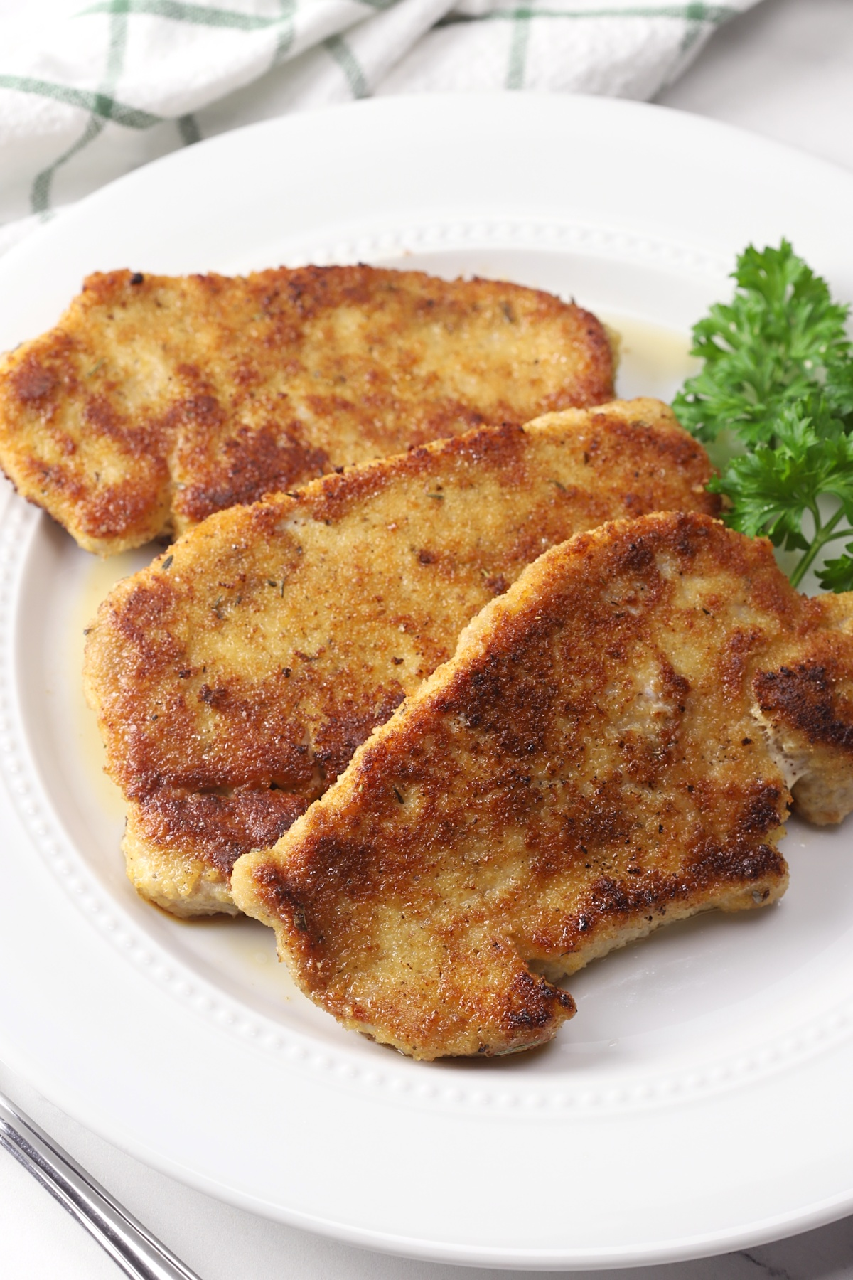 Three breaded pork chops on a white plate.